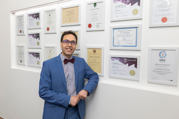 Dr Moh in front of wall of university degrees