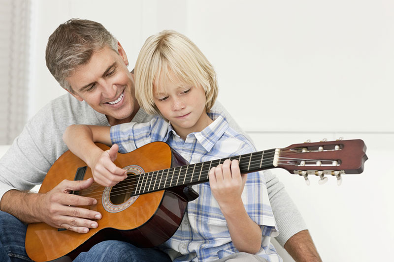 father and son plaing guitar